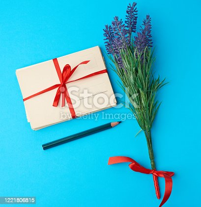 tied red silk ribbon rectangular vintage greeting card, blue background, top view