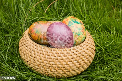istock Tie-dyed Easter Eggs in the wicker basket 473483590