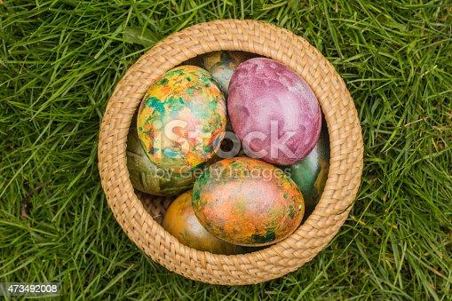 istock Tie-dyed Easter Eggs in Wicker Basket 473492008