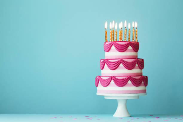 Tiered birthday cake with golden candles Pink tiered birthday cake with birthday candles cakestand stock pictures, royalty-free photos & images
