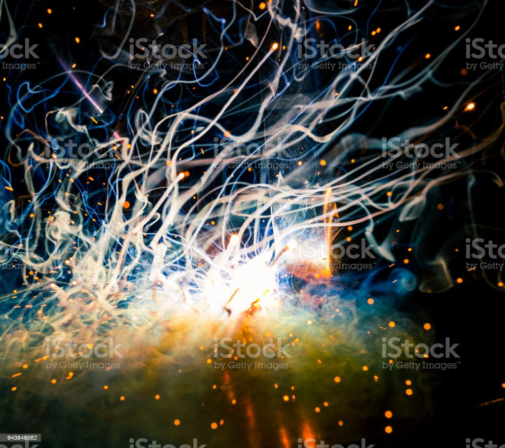 Tig welding dual core plasma flux blast of energy, light, smoke, sparks, and flame creation stock photo