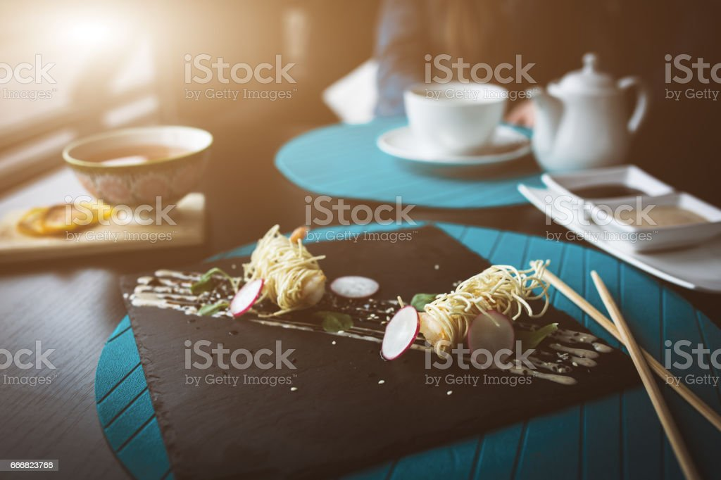 Tiger shrimps in Chinese noodles with sauce on black plate. Asian food concept. People on background in restaraunt place with wooden table. Flare copy space for text, design stock photo