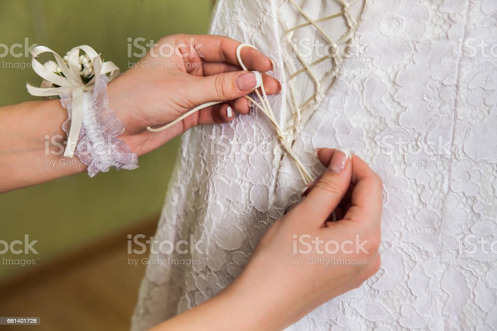 tighten wedding dress on bride stock photo
