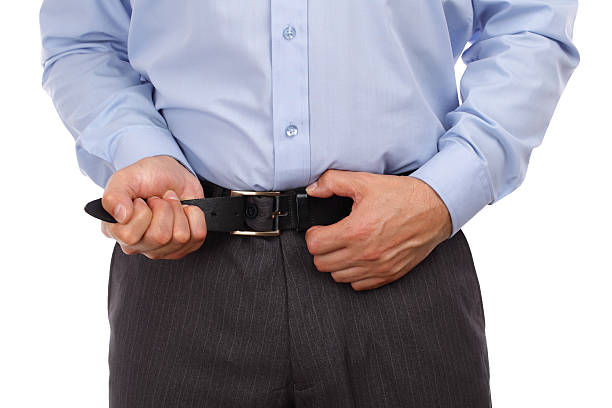 Tightening one's belt Businessman tightening his belt concept for recession or economic depression tighten stock pictures, royalty-free photos & images