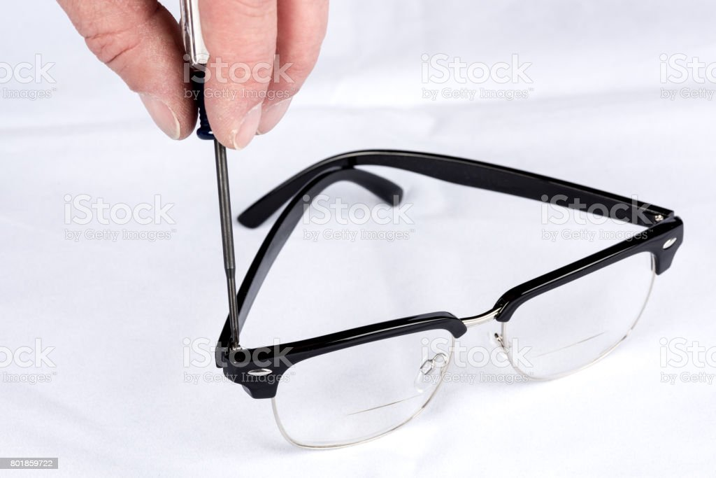 Tightening The Small Screw On A Pair Of Glasses Stock Photo Download Image Now Istock
