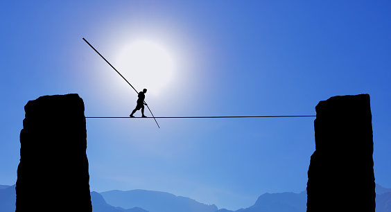 Highline walker in blue sky between two rocks concept of risk taking and challenge