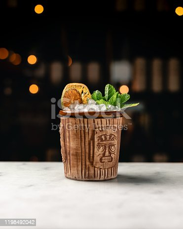 A tiki cocktail in a classic tiki cup. The Mai Tai cocktail with mint sprig and a dried lime and lemon wheel