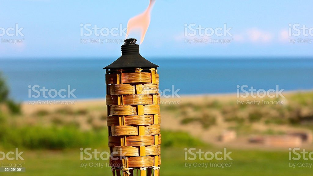 Tiki Torch along lakefront on a summer late afternoon stock photo