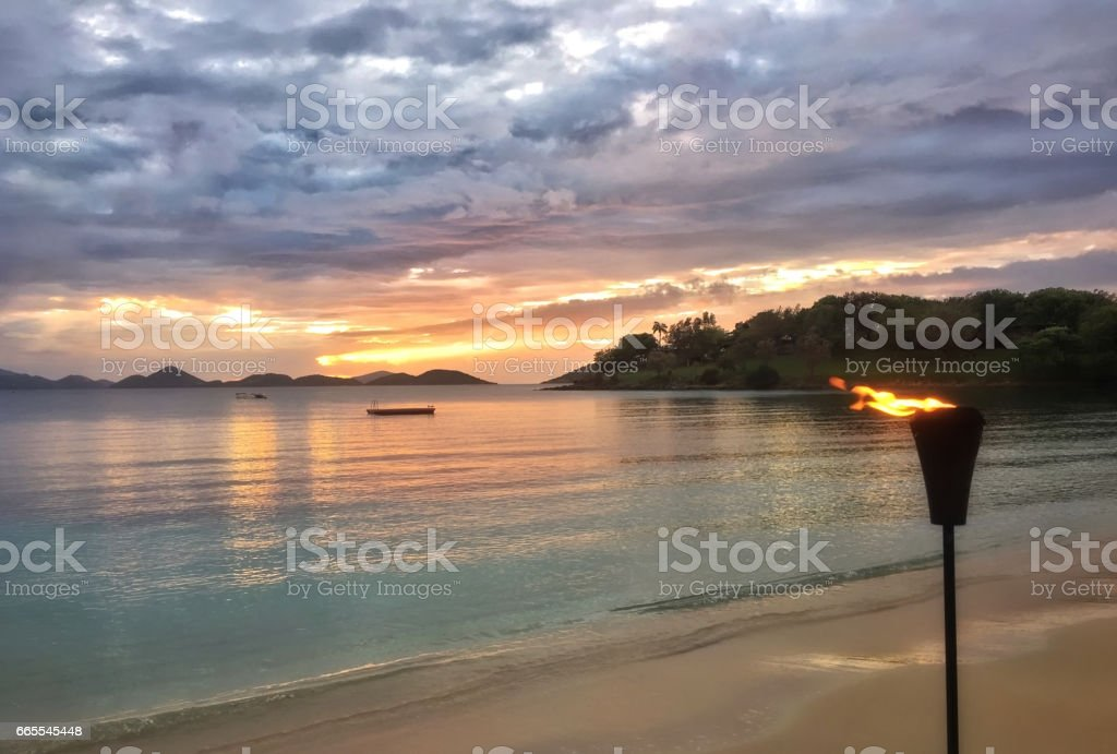 tiki torch on virgin islands beach sunset with stormy skies