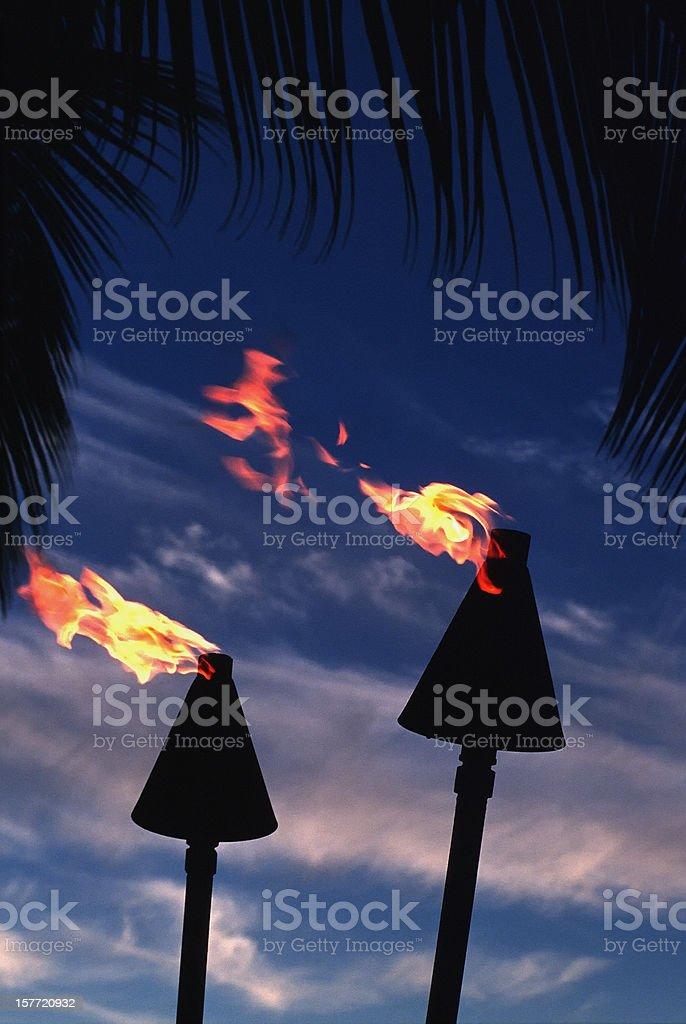 Tiki Torches at Sunset, Tropical Symbol, Night, Dramatic Sky, Paradise royalty-free stock photo