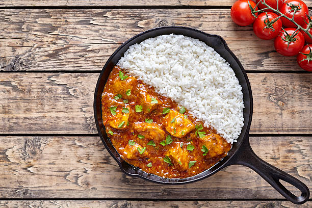Tikka masala traditional butter chicken spicy meat food and rice Tikka masala traditional butter chicken spicy meat food and rice with tomatoes in cast iron skillet on vintage wooden background. Karahi chicken recipe balti dish stock pictures, royalty-free photos & images