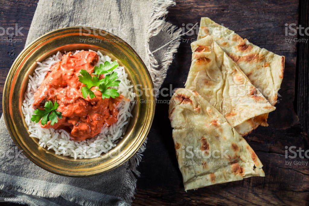 Tikka masala with rice and chicken served with Naan bread stock photo