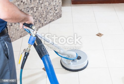 Man cleaning tile and grout with machine in bathroom