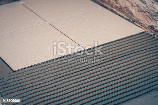 istock Tile glue is gently applied to the floor with even lines using a notched trowel 918805966