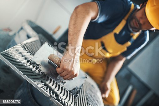 Closeup of a handyman applying adhesive with a trowel material onto a tile before installing it on a bathroom wall. He's wearing yellow uniform and helmet. Tilt shot, selective focus.