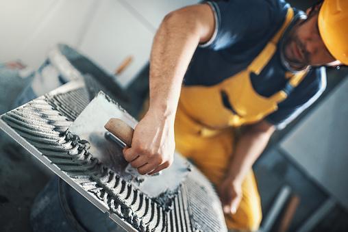 Tile handyman applying adhesive on a tile.