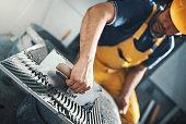 istock Tile handyman applying adhesive on a tile. 638506270