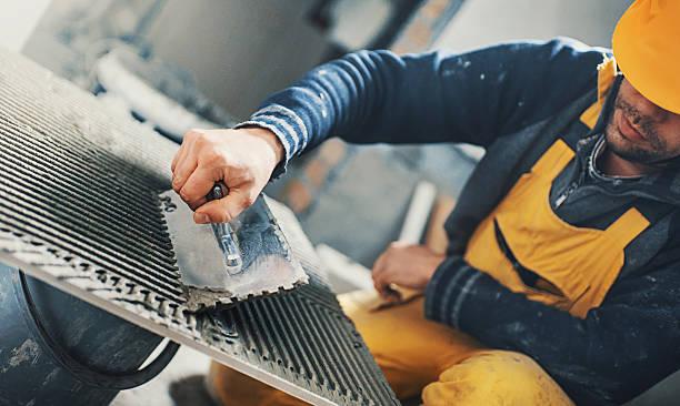 tile handyman applying adhesive on a tile. - fliesenkleber stock-fotos und bilder