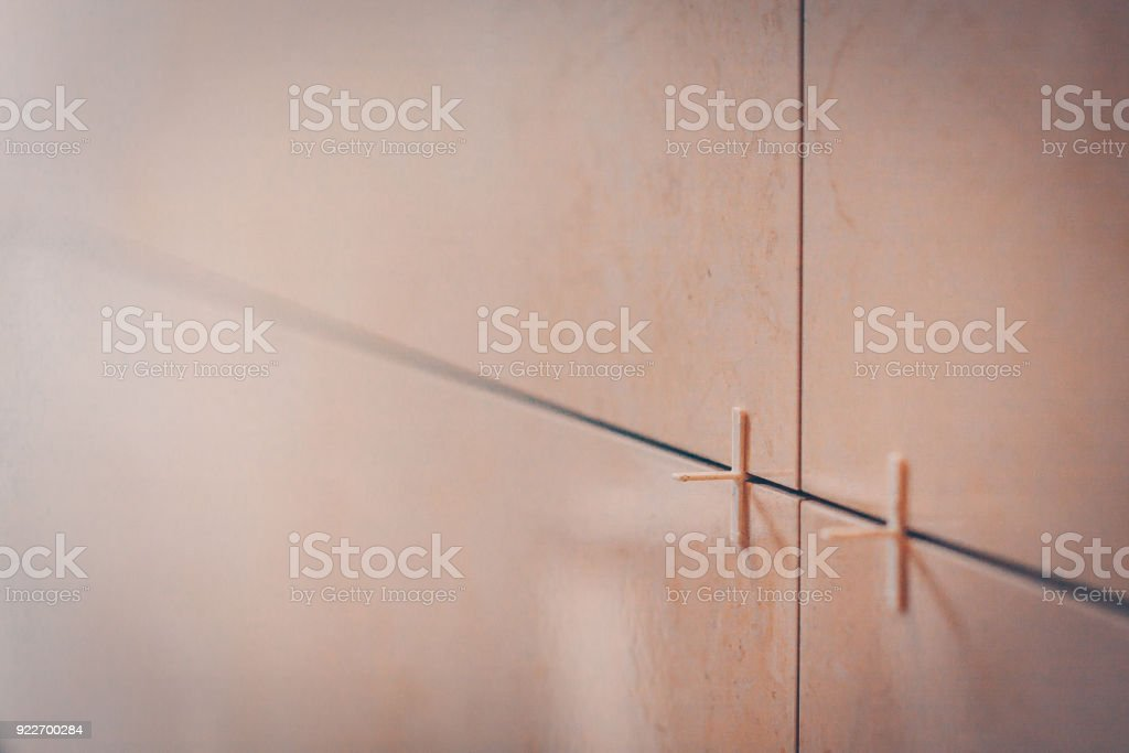 Tile on the wall close-up in the defocus, technology of tiling and finishing stock photo