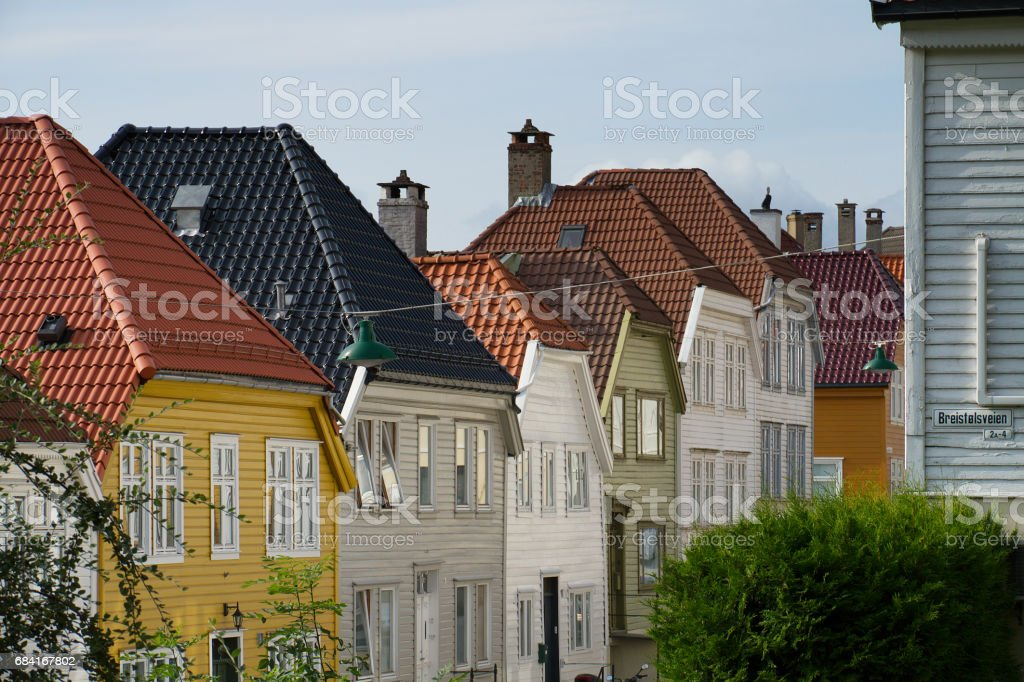 Tile roofs of Bergen, Norway and green street lamps стоковое фото