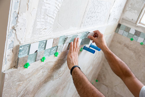 tile series:tile border being installed on shower wall in home - jodijacobson stock pictures, royalty-free photos & images