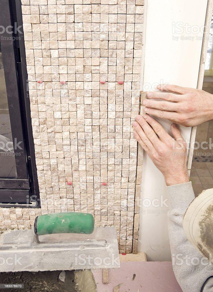 Tile Setter installing Border Stones for Fireplace Surround stock photo