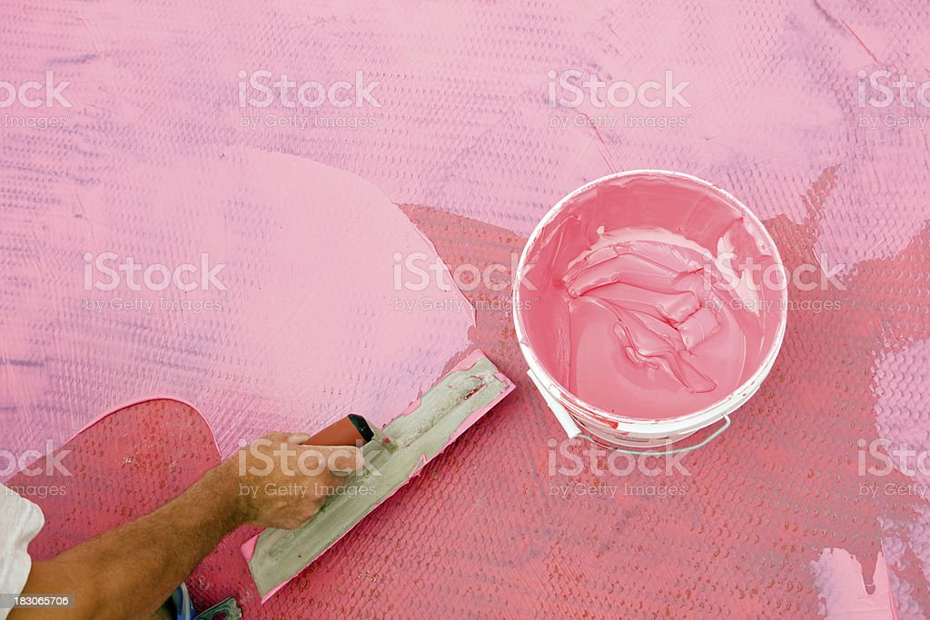 Tile Setter Spreading Waterproof Membrane on Laundry Room Floor royalty-free stock photo