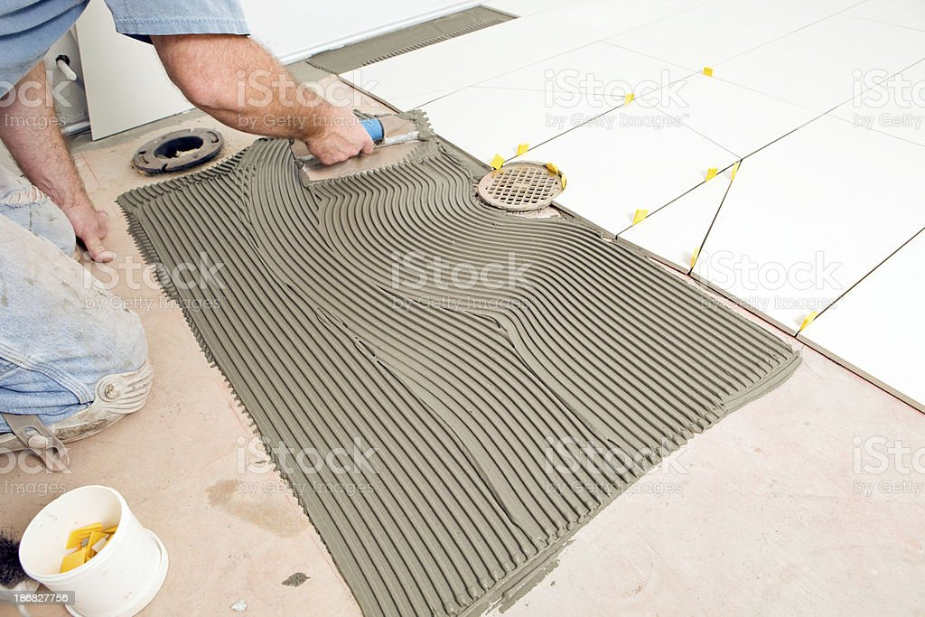Tile Setter Troweling Mortar on a Concrete Floor royalty-free stock photo