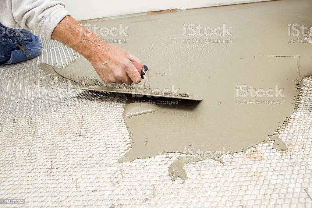 Tile Setter Troweling Mortar on Mesh Subfloor royalty-free stock photo
