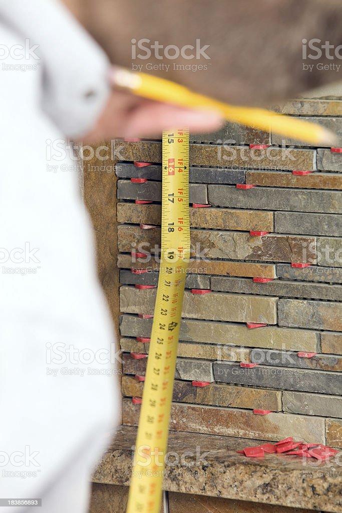 Tile Worker Measuring a Stacked Stone Backsplash stock photo