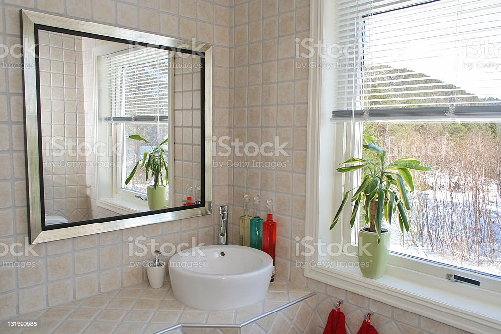 A tiled bathroom with a modern sink and mirror royalty-free stock photo