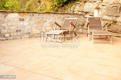 Horizontal colour image with warm tones of a patio which is tiled. The flooor tiles are ceramic and terracotta with warm earthy tones. Laid diagonally. Natural stone wall in background made by local artisan with rockface seen behind chair on the right. Two wooden patio chairs ready for any covers or cushions to be inserted.