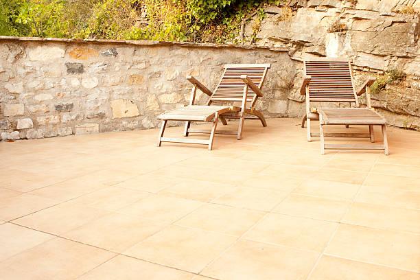 gefliesten terrasse mit zwei stühlen aus holz und stein mauer - naturstein terrasse stock-fotos und bilder