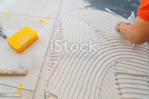 1138442636 istock photo Tiler and plaster repair work laying tile, trowel in a man hand 1143916943