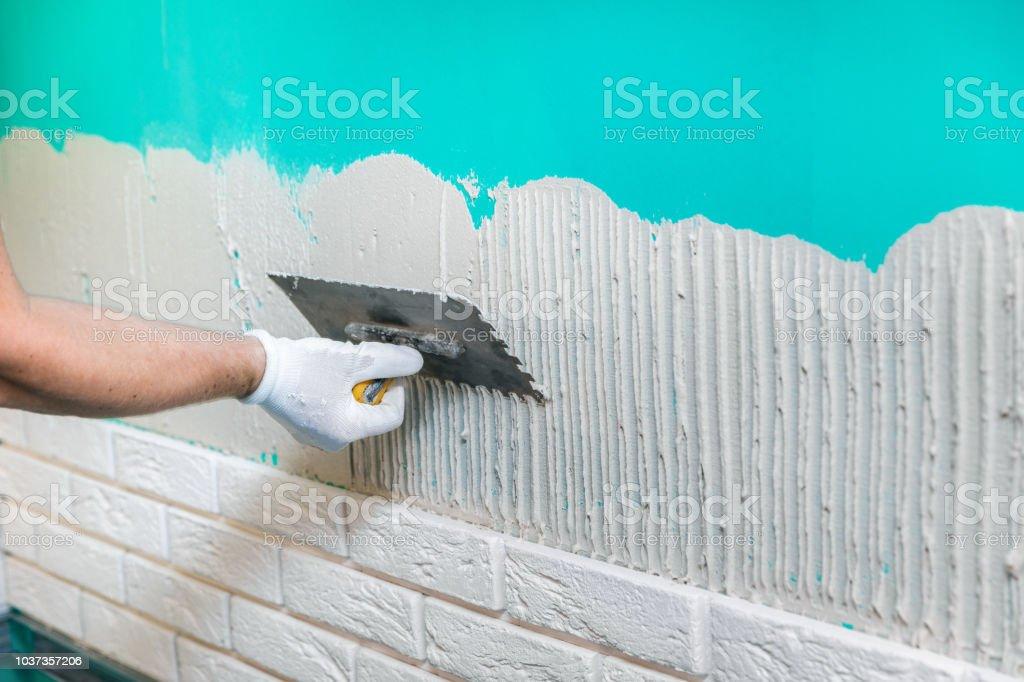 tiler applying tile adhesive on the wall stock photo