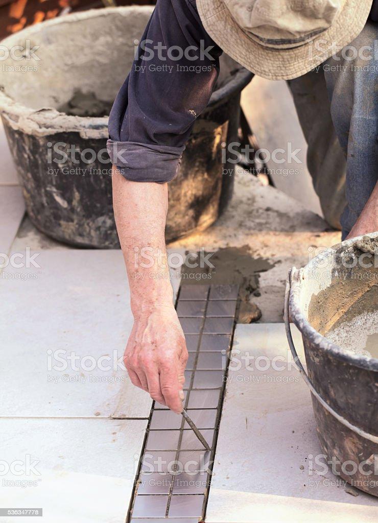Fliesenleger reinigt Fugen - Lizenzfrei Anstrengung Stock-Foto