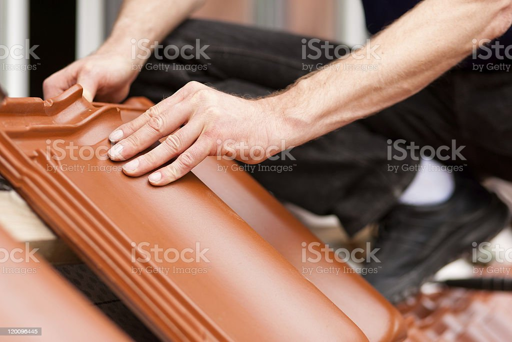 Tiler covering roof with new tile royalty-free stock photo
