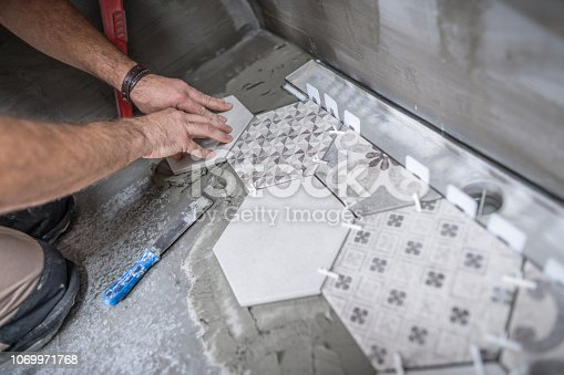 Anonymous image of male constructor aligning and pressing ceramic tile on the floor