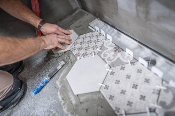Tiler installing ceramic tiles on the bathroom floor stock photo