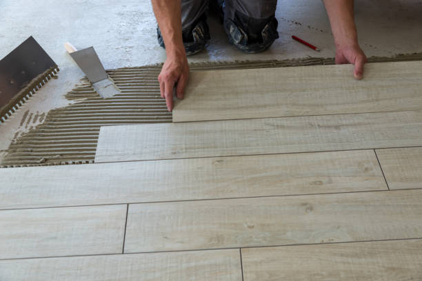Carreleur pose des carreaux de céramique. - Photo