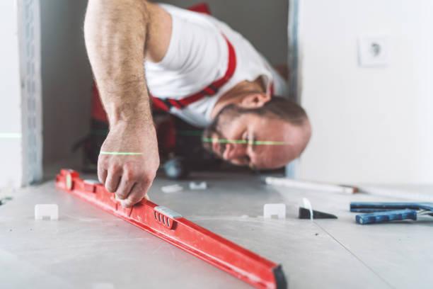 fliesenleger mess- und nivellierung der fliesenboden - diy beton stock-fotos und bilder