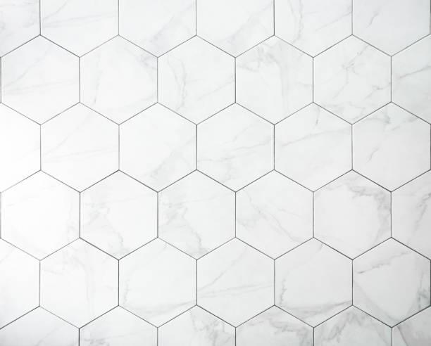 tiles. a white marble wall with hexagon tiles for texture and background. - azulejo imagens e fotografias de stock