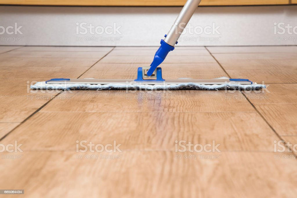 Tiles floor washing with mop in the room. Regular clean up. Maid...