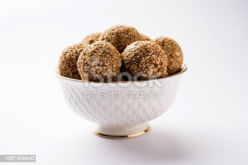 istock Tilgul Laddu or Til Gul balls for makar sankranti, it's a healthy food made using sesame, crushed peanuts and jaggery. served in a bowl. selective focus showing details. 1087405640
