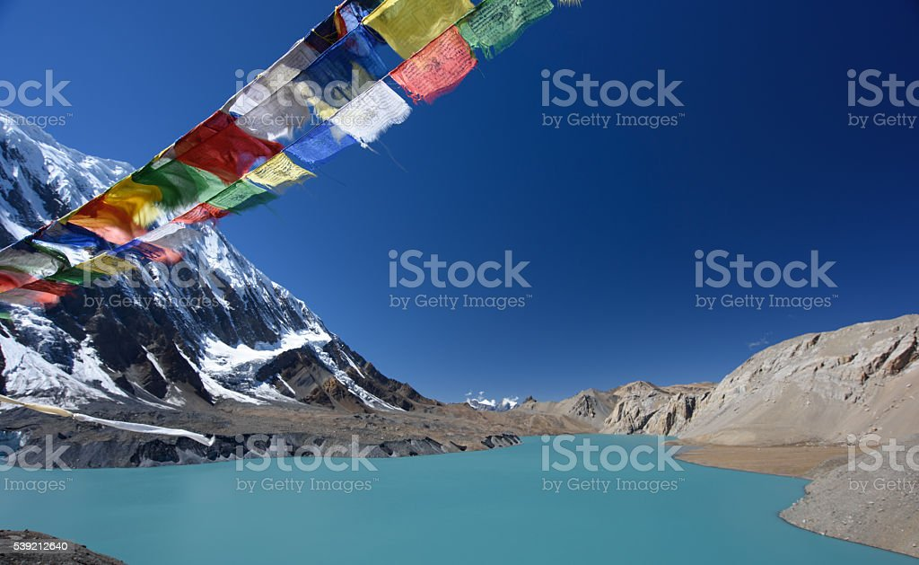 Tilicho lake and prayer flags in Nepal stock photo