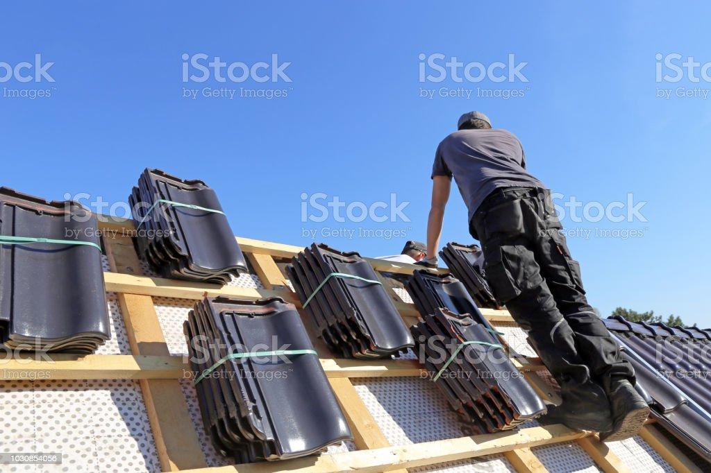 Ein Dach mit Ziegeln zu decken - Lizenzfrei Arbeiten Stock-Foto