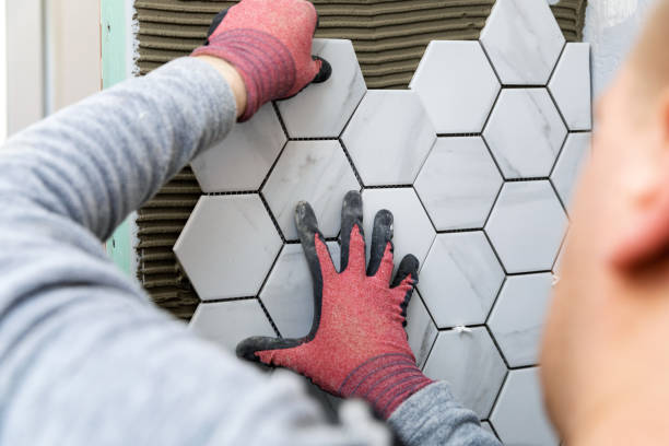 tiling - man laying marble texture hexagon tiles on the wall stock photo