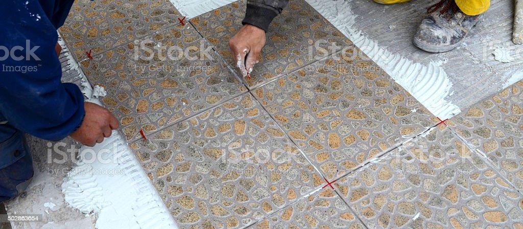 Tiling the floor stock photo
