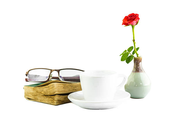 till life white cup and pink zinnia book and glasses stock photo