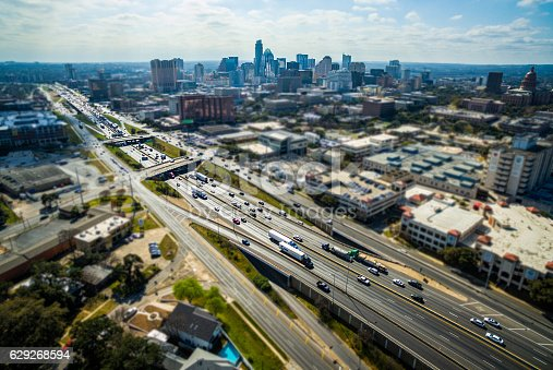 Tilt Shift Austin Texas Aerial Interstate blurred surrounding with busy interstate 35 running right down the center of Texas and the Texas State Capitol building and Skyline background